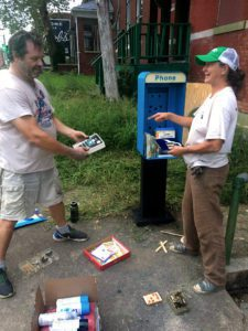 Dutchtown Volunteers Benjamin Thomas and Terri Zeman prepare the old pay phone stand for conversion to a free little library.