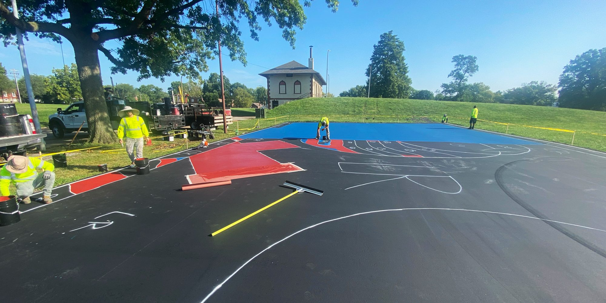 Workers painting the mural on the futsal court at Marquette Park.