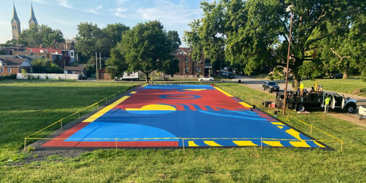 Putting the finishing touches on the futsal court mural at Marquette Park.
